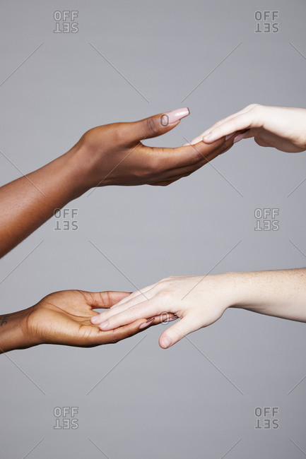 Crop unrecognizable multiethnic females touching and holding hands as greeting and equal gesture on gray background in studio