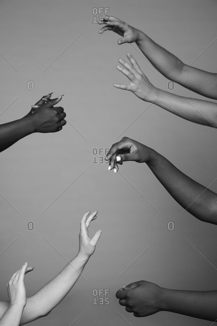 Black and white crop faceless company of diverse females standing in studio with delicate raised arms on gray background