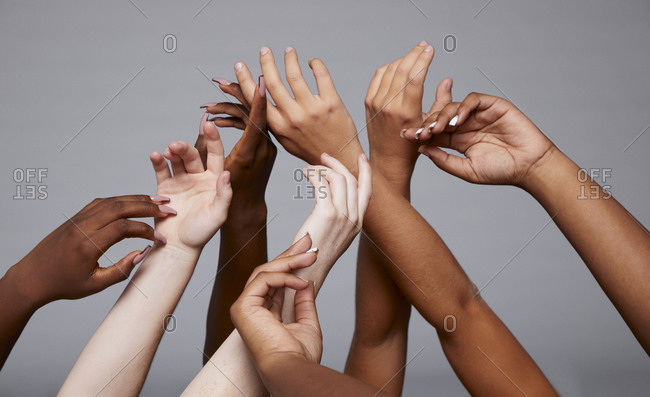 Crop faceless company of diverse females standing in studio with delicate raised arms on gray background