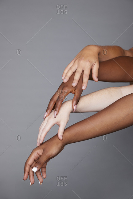 Group of unrecognizable crop multiracial females with different skin tone stacking hands delicately on gray background in studio demonstrating racial equality