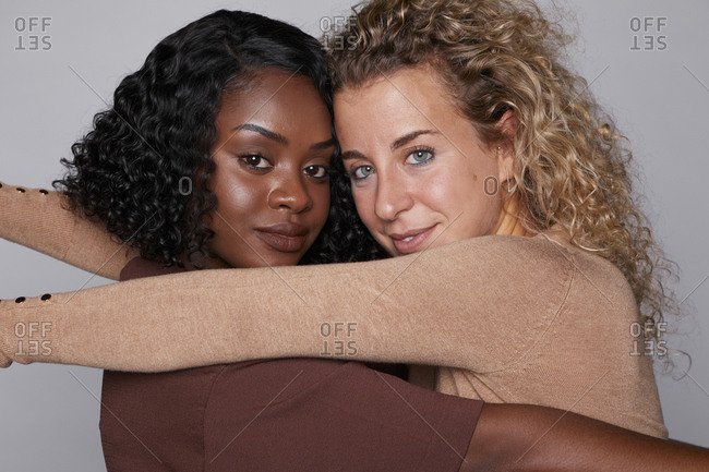 Side view of content multiethnic female friends tenderly cuddling on gray background while standing face to face and looking at camera