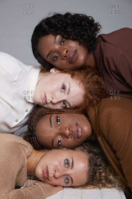 Company of multiethnic females with braids and curly hair touching heads face to face on gray background in studio and looking at camera