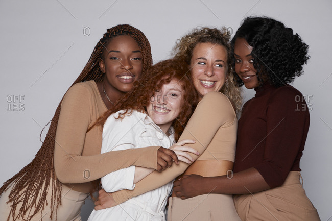 Company of cheerful multiethnic females with braids and curly hair hugging together and laughing while gathering in modern studio looking at camera