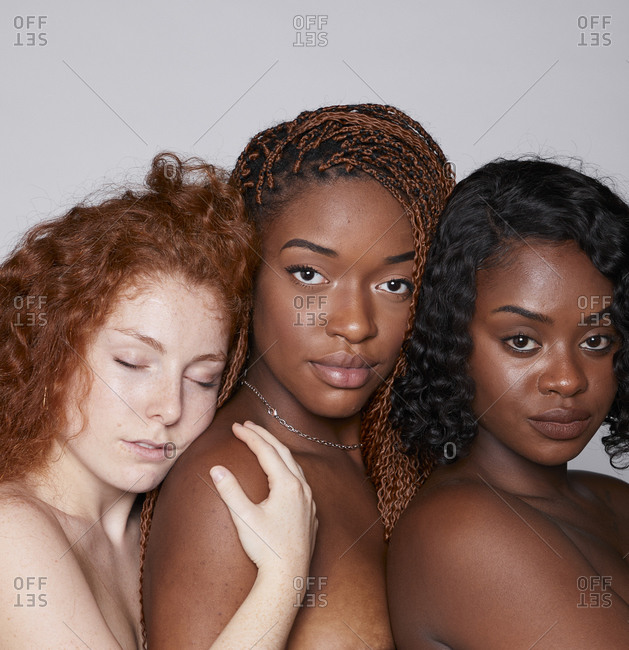 Tranquil multiracial females with bare shoulders cuddling tenderly on gray background in studio
