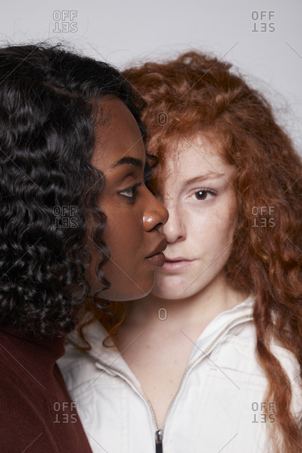 Unemotional multiracial females with red curly hair and ethnic african brunette with standing face to face on gray background in studio
