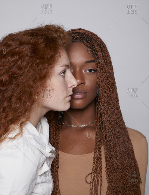Unemotional multiracial females with red curly hair and brown hair with braids standing face to face on gray background in studio