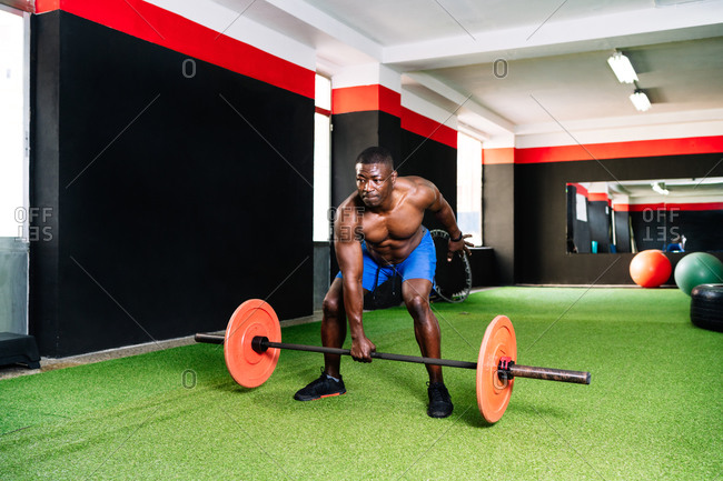 Strong African American male bodybuilder with muscular torso lifting heavy barbell during training in modern sports center
