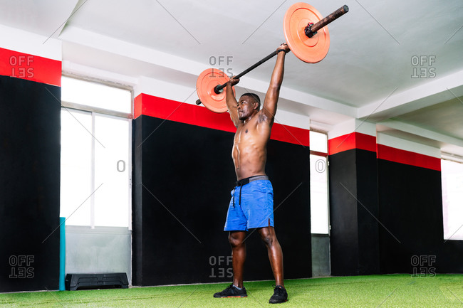 Side view of strong African American male bodybuilder with muscular torso lifting heavy barbell during training in modern sports center