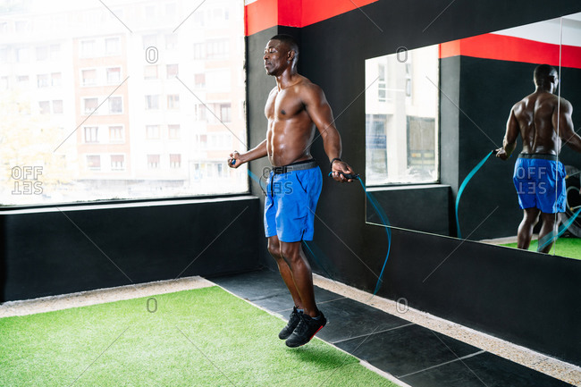 Sweaty African American sportsman with muscular body skipping rope in modern bright fitness center during functional workout