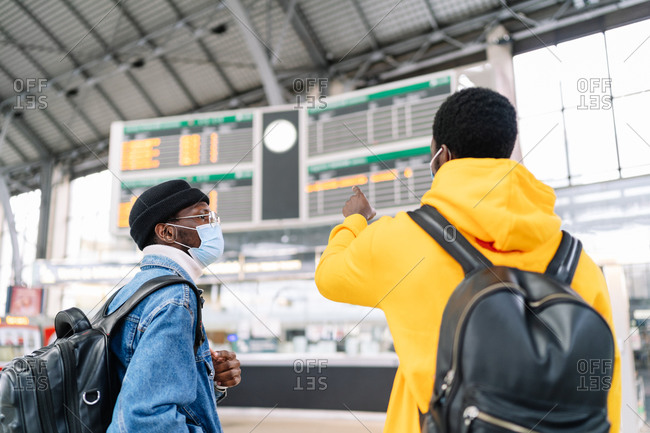Traveling ethnic male friends with backpacks and in medical masks checking information on train schedule at station before departure during coronavirus epidemic