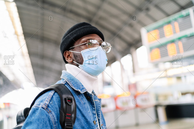 Side view of African American male traveler in medical mask standing on railway station with timetable and waiting for departure
