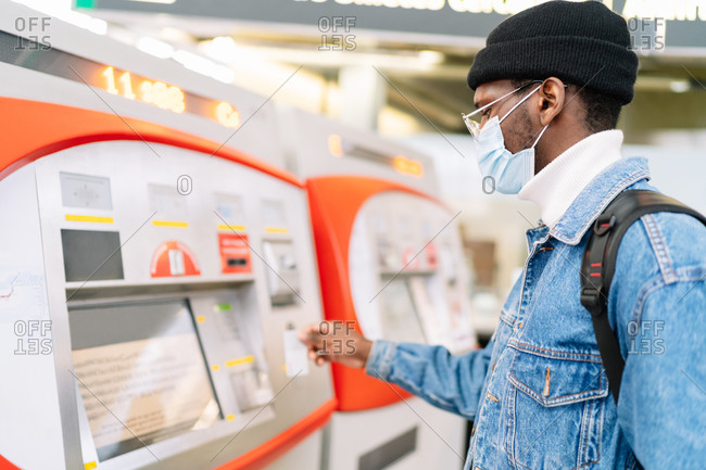 Side view of African American male traveler in mask buying ticket in self service machine on railway station during coronavirus pandemic
