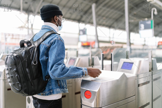 Side view of African American male tourist with backpack passing through turnstile on railway station while traveling during coronavirus pandemic