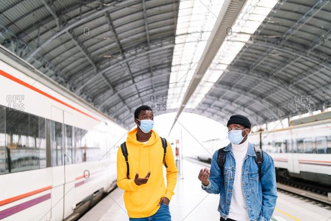 African American traveling males wearing protective masks walking along railway platform and talking before departure
