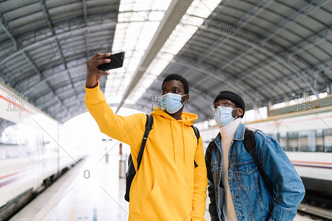 Ethnic male friends in medical masks taking self portrait on smartphone while standing on platform and waiting for train