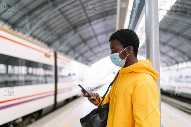 Ethnic male traveler with backpack and in mask standing on platform with train and using cellphone while waiting for departure during COVID 19 epidemic