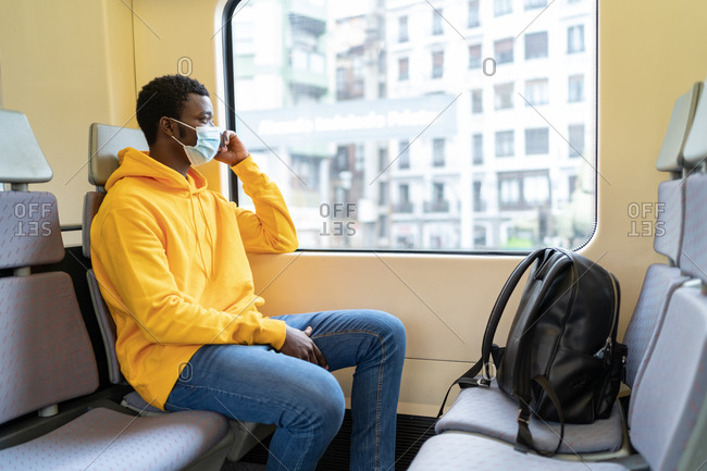 Side view of smiling African American male tourist in mask sitting on passenger seat in contemporary train and looking out of window while traveling during coronavirus epidemic