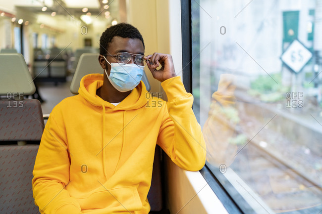 African American male tourist in mask sitting on passenger seat in contemporary train and looking out of window while traveling during coronavirus epidemic