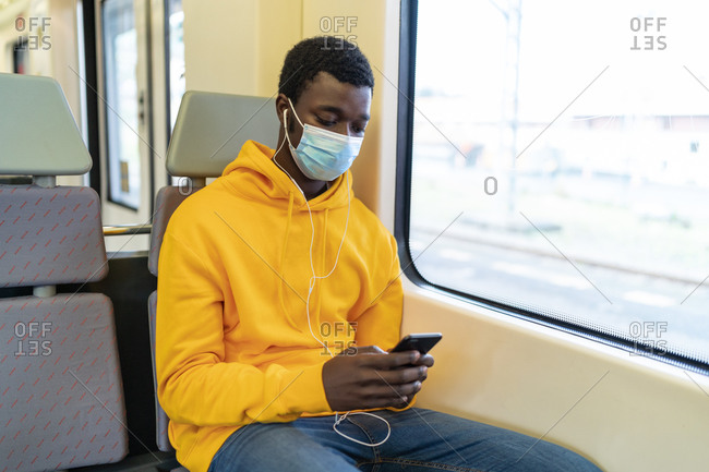 Calm African American male tourist in protective medical mask sitting on passenger seat in modern train and browsing smartphone during trip