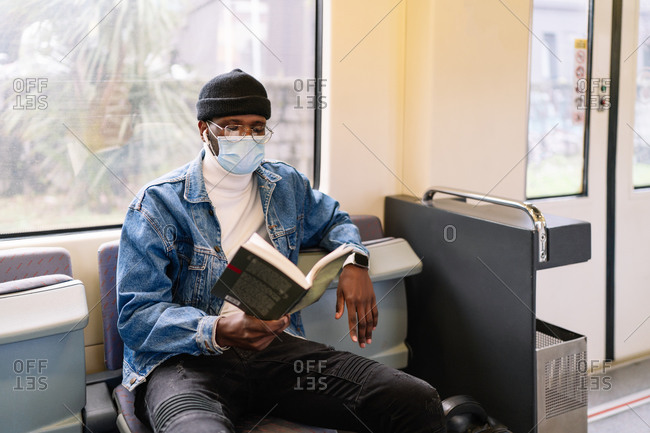 Serious African American male in medical mask sitting on passenger seat in modern train and reading book during coronavirus pandemic