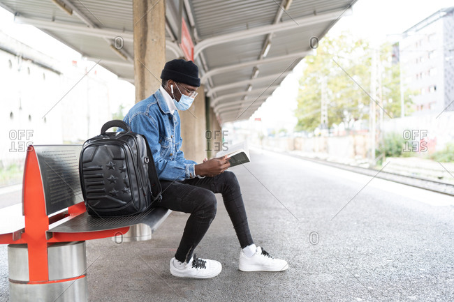Side view of black male traveler in medical mask sitting on bench and reading book while waiting for train on railway platform