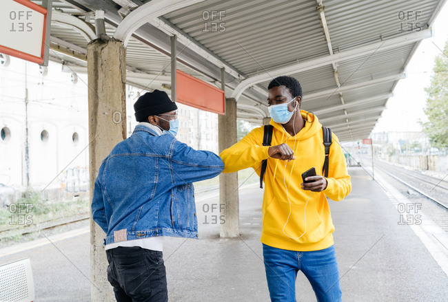 Side view of cheerful African American friends in medical masks bumping elbows while greeting each other during COVID 19 epidemic