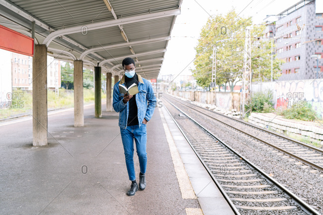 African American male traveler in medical mask during coronavirus pandemic standing on railroad platform with book while waiting for train and looking away