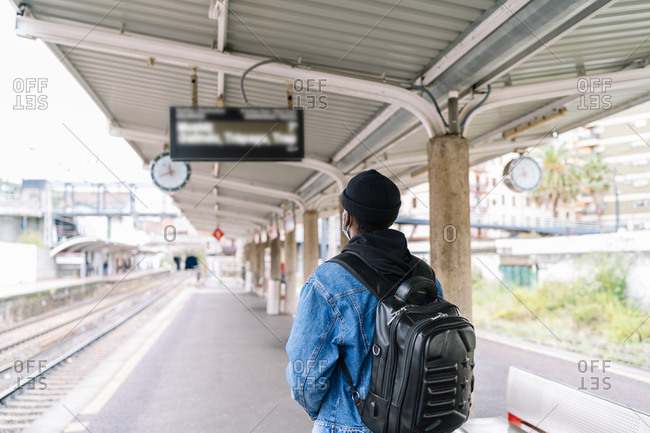 Back view of ethnic male tourist in mask and with backpack standing on platform of railway station during coronavirus epidemic
