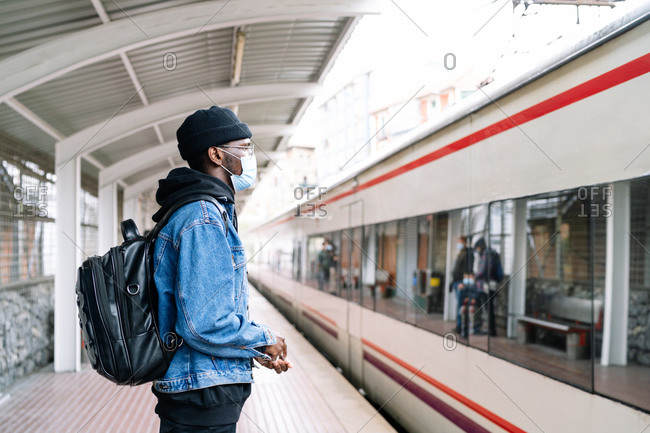 Side view of ethnic male tourist in mask and with backpack standing on platform of railway station during coronavirus epidemic