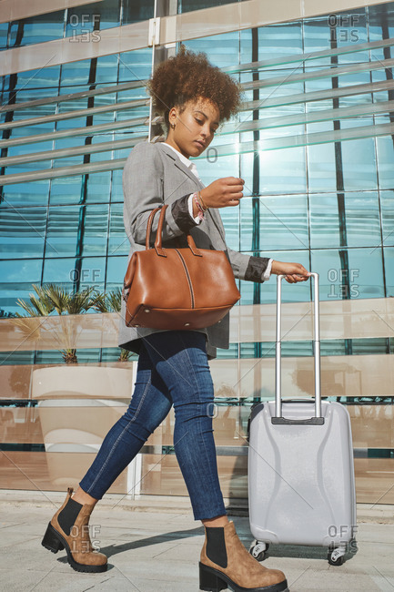 Serious African American female entrepreneur in smart casual outfit and with suitcase walking in airport