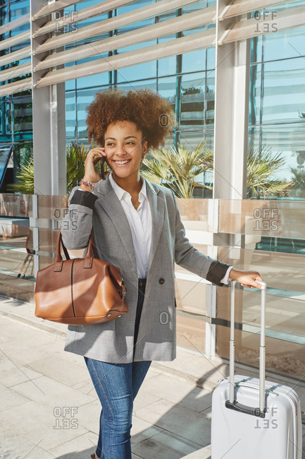 Cheerful African American female entrepreneur in smart casual outfit and with suitcase standing in airport and speaking on smartphone