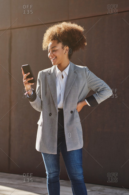 Positive ethnic female entrepreneur in smart casual style using smartphone while standing on street