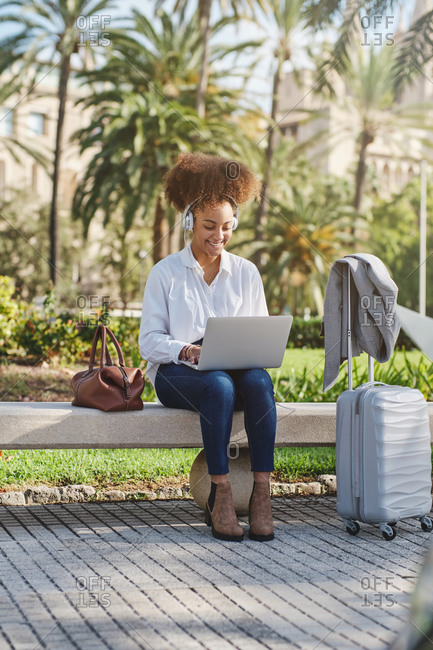 Positive African American businesswoman sitting on bench near suitcase and typing on laptop while working on remote project