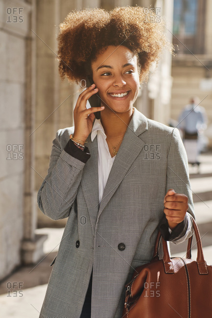 Delighted African American female in smart casual style walking in city on sunny day and speaking with friend on cellphone