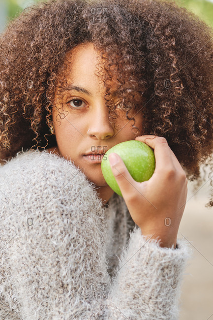 Unemotional African American female in warm sweater and with Afro hairstyle sitting with green apple and looking at camera