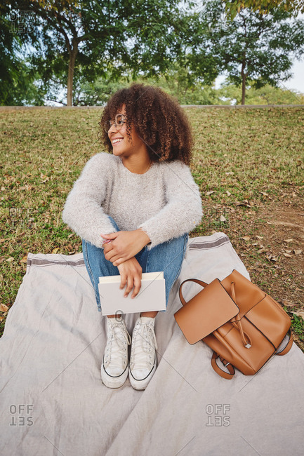 Young carefree black female in casual outfit sitting on blanket with book in garden and looking away while entertaining at weekend