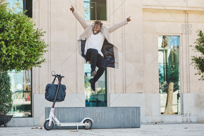 Delighted African American guy in casual outfit in moment of jumping above street with electric scooter in city