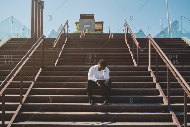 Exhausted African American young male sitting in staircase on street and leaning on hand while relaxing