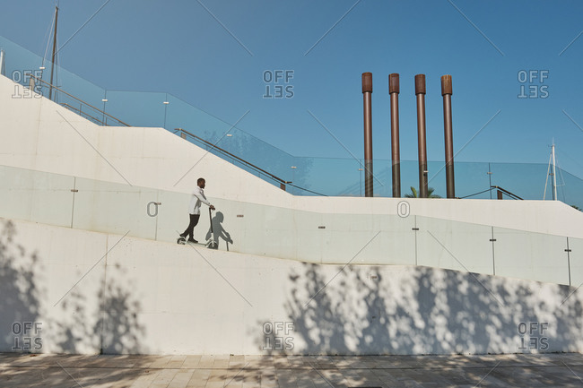 Side view of ethnic male riding modern electric scooter down concrete slope in city on sunny day