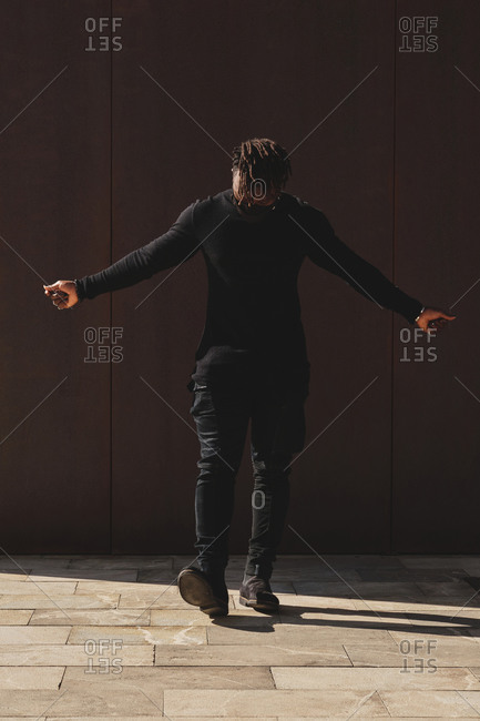 Cool African American male wearing trendy casual clothes and protective mask standing on street in city during coronavirus epidemic