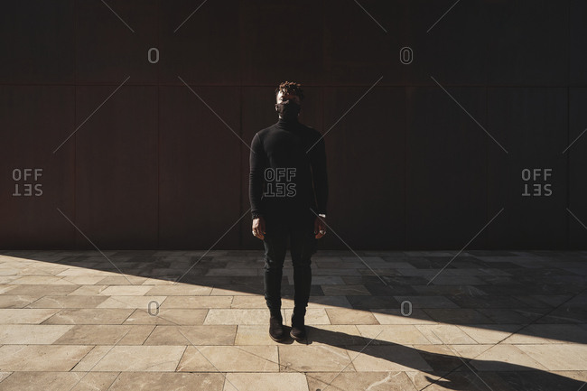 African American male in black outfit and protective mask standing on street and looking at camera during COVID 19 epidemic