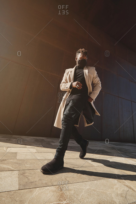 Low angle of African American male in trendy brown coat walking in city in mask during COVID 19 pandemic and looking away