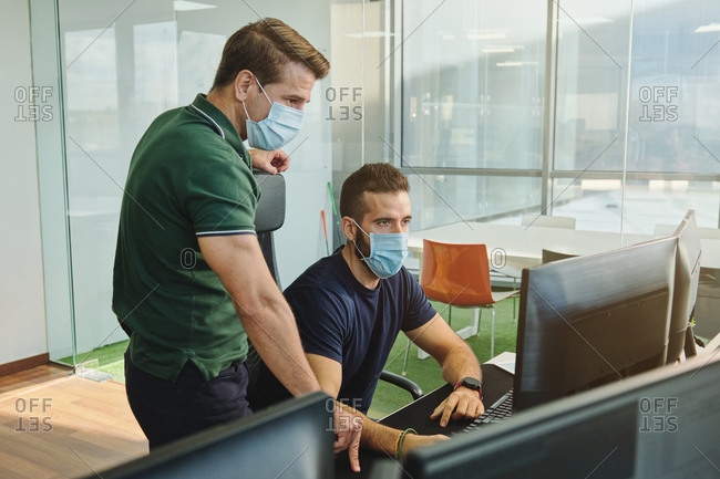 From above of male coworkers in medical masks together using program for software during coronavirus pandemic