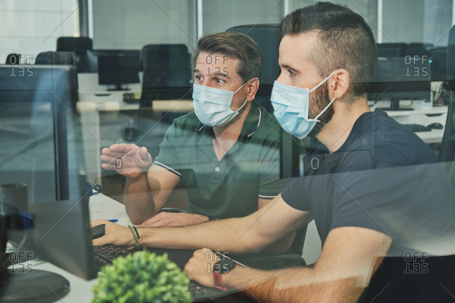 Male coworkers in medical masks sitting together using program for software during coronavirus pandemic