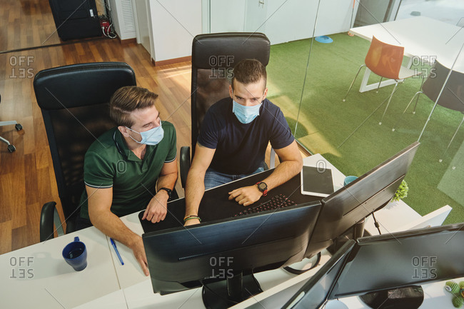 From above of male coworkers in medical masks sitting together using program for software during coronavirus pandemic
