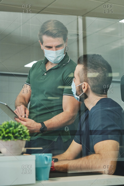 Serious male colleagues in medical masks discussing project while working on software development in modern office