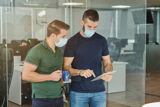 Busy male programmers in medical masks standing with tablet in office and discussing software development at work during coronavirus outbreak