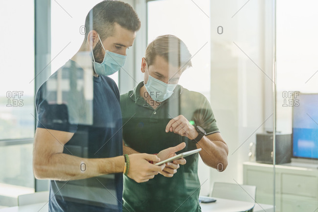 Through glass busy male programmers in medical masks standing with tablet in office and discussing software development at work during coronavirus outbreak