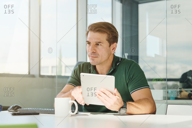 Concentrated male software developer sitting at table in modern workplace and browsing tablet while working on program code