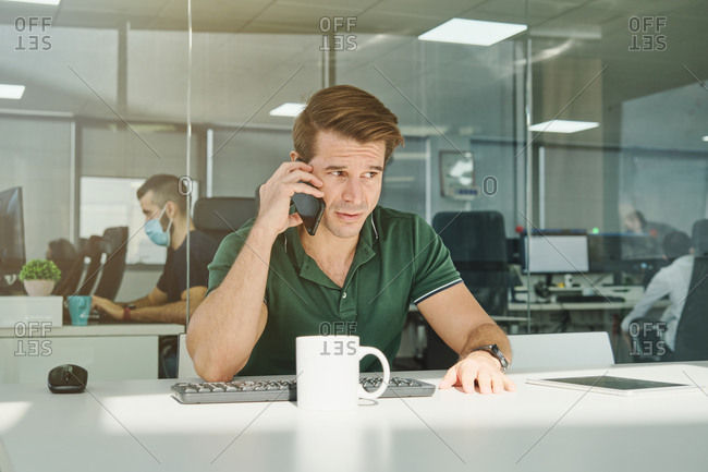 Smiling male employee sitting at table in workplace and discussing project on cellphone at working day
